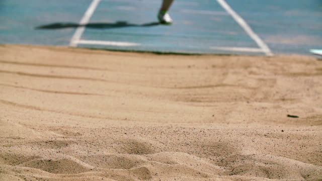 Track and field athlete in slow motion doing long jump video