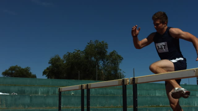 Track athlete jumps over hurdle, slow motion video