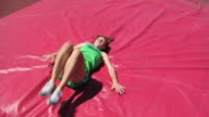 Track athlete lands on mat in high jump event video