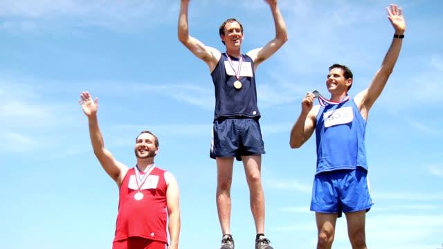 Track athletes on podium celebrating video