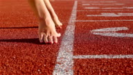 Track runner woman putting her hands at starting line video
