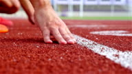 Track runners putting hands at starting line, slow motion video