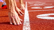 Track runners putting hands at starting line video