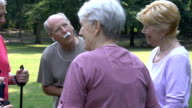 Tracking shot of active seniors communicating in park video