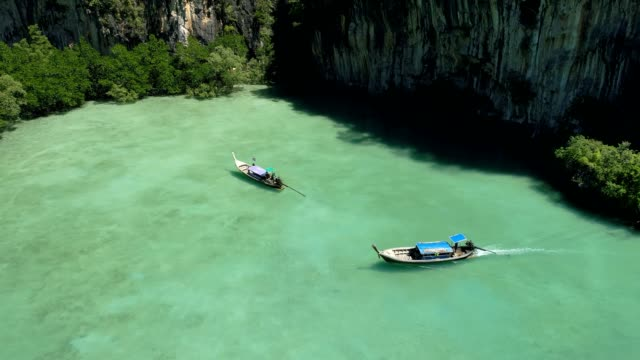 Tracking shot of longtail boats navigating in beautiful lagoon video