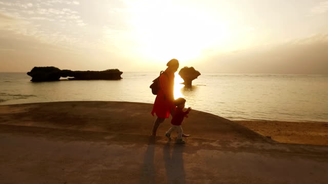 Tracking shot of mother and daughter walking on the beach. video