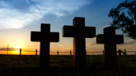 Tracking shot of Three massive stone crosses on the graves of the old cemetery against time lapse of clear blue sky with moving sun. video