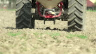 CLOSE UP: Tractor fertilizing the field with manure in spring video