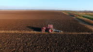 Tractor plowing a field, aerial shot. video