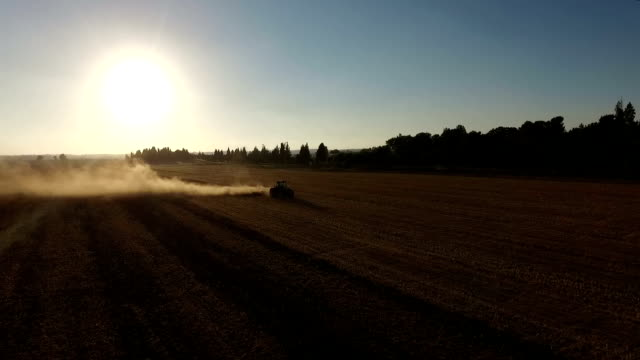AERIAL: Tractor plowing field at sunset. video