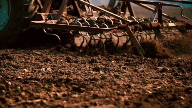 Tractor plowing field at sunset video