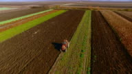 Tractor plowing on a rural farm land aerial video