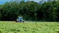 Tractor pulls on the field, agricultural mechanism for weeding plants. On a clear sunny day on a background of green forest video