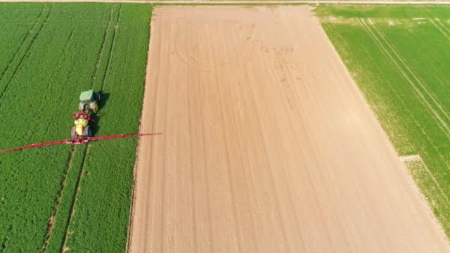 Tractor Spraying Crop Field In Spring Flyover video