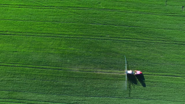 Tractor Spraying Crop Field In Spring Flyover video