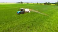 Tractor sprinkles bean field video