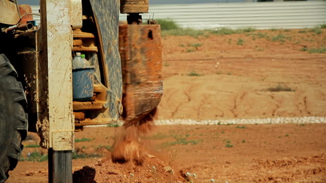 Tractor with a drilling device at a construction site video