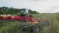 Tractor working in the field, collecting in a row green grass video