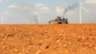 Tractors running on farmland With Wind turbine video