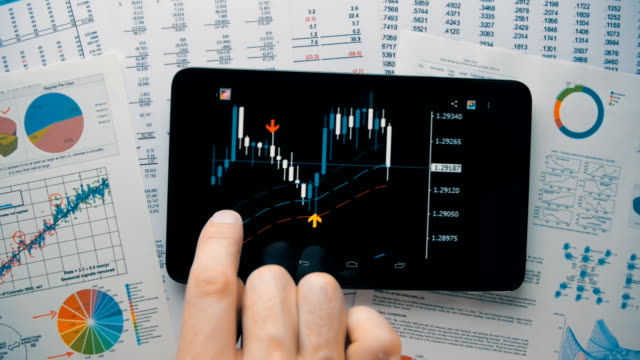 Trader moving graphics currency quotes on the screen of the tablet video