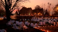 Traditional buddhist people are lighting candles for religious ceremonies video