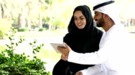 Traditional Emirati young couple outside with digital tablet - slowmotion video