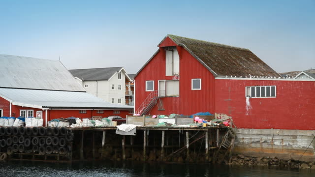 Traditional Norwegian fishing village scene. Red wooden houses and packed fishing nets lies on the coast video