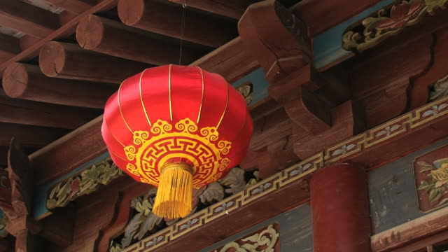 Traditional red Chinese lantern hangs with an aged carved and painted wooden building background. video