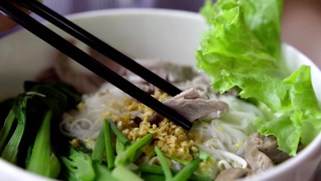 Traditional Vietnam Pho Bo (beef noodle soup) with someone eating it. Close-up video