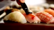 Traditionally applying soy sauce on top of sushi with brush video