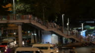 Traffic and city commuters walk crossing pedestrian footbridge in Asia video