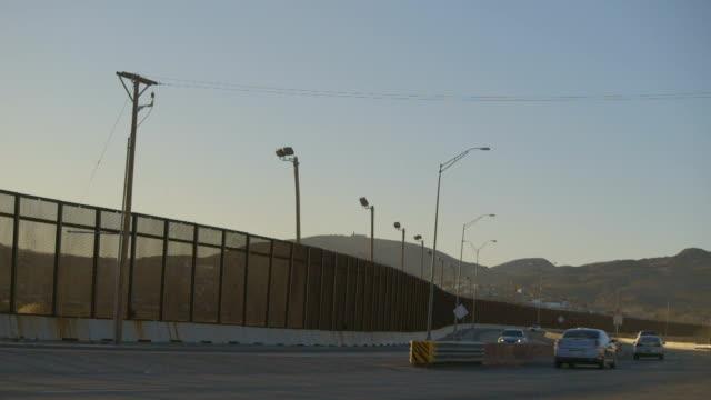 Traffic Driving Toward Mountains Near Border Fence video