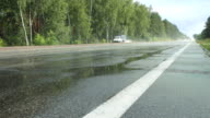 Traffic on wet road highway with mist splash video