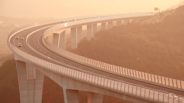 Traffic rushing by on a viaduct at sunset video