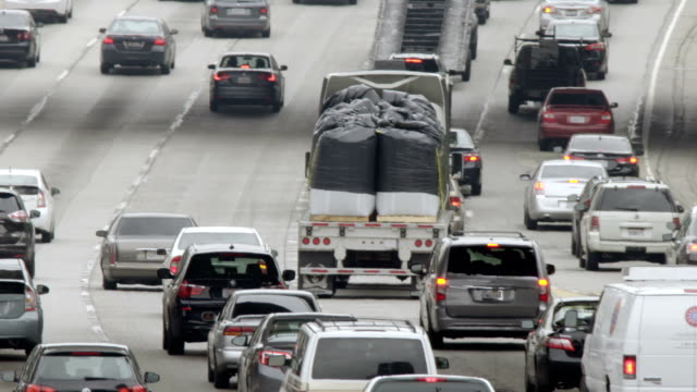 Traffic with truck full of sacks heads north on 110 freeway in Downtown LA video