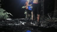 Trail run competitors running across a muddy road at night video