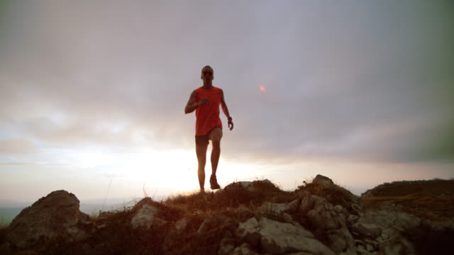 SLO MO trail runner running on the ridge in sunset video