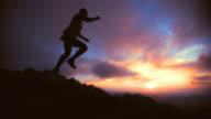 SLO MO trail runner silhouette jump video