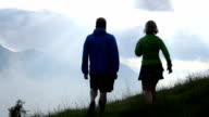 Trail running couple ascend slope through mountain meadow video