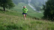Trail running woman ascends slope through meadow video