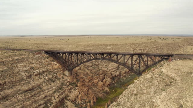 AERIAL: Train crossing steel arch railroad bridge across the Canyon Diablo video