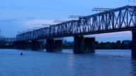 Train moving ahead on overpass bridge against night river. video