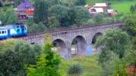 train rides through a village in the mountains video