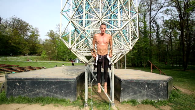 Trained man exercising on gymnastics rings video