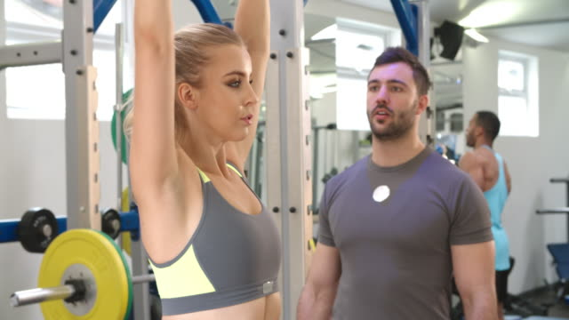 Trainer advising a woman exercising with dumbbells at a gym video