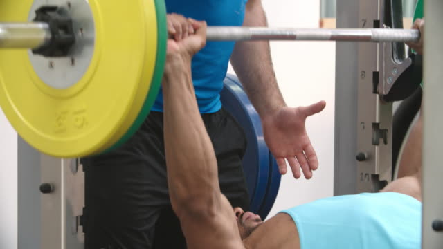 Trainer assisting man bench pressing barbells at a gym video