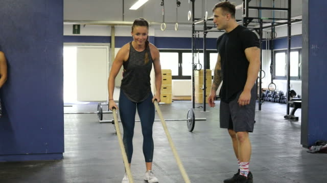 Trainer clapping for woman exercising with ropes video