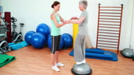 Trainer helping elderly client to use bosu ball video