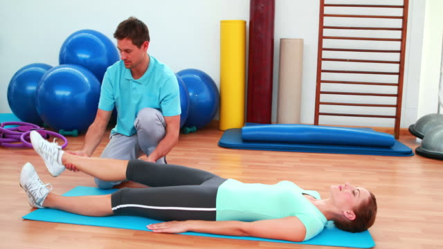 Trainer helping his client bend her knee video