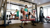 Trainer helping his client bend her leg on the bench. video